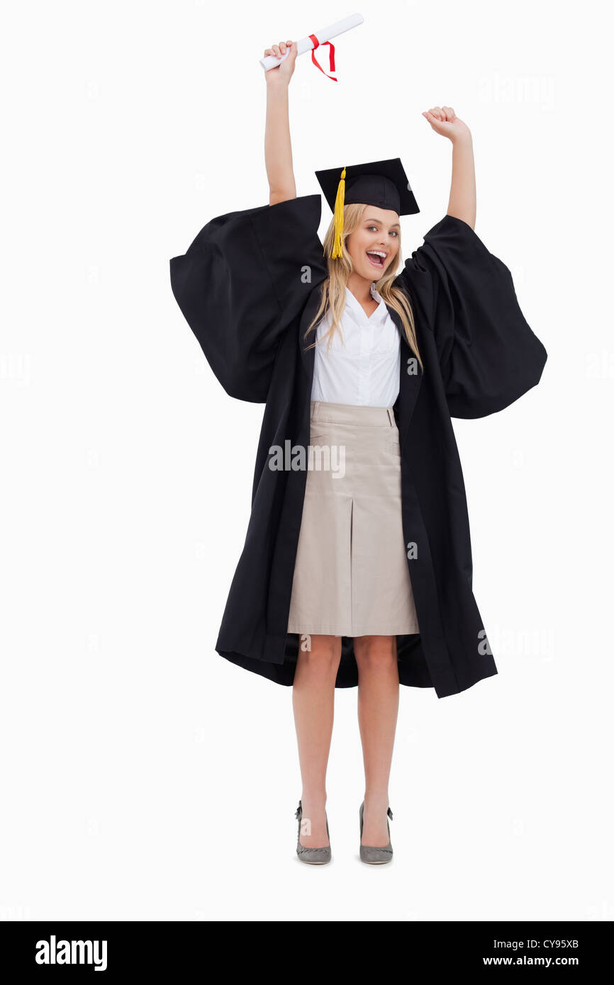 Blonde student in graduate robe holding up her diploma - Stock Image