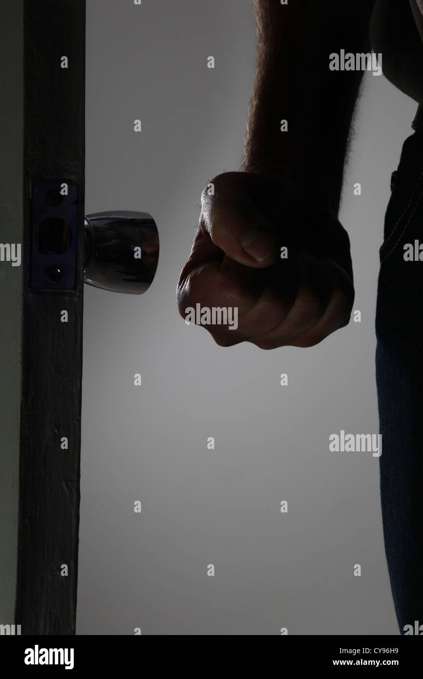 Male fist clenched entering a dark room. Model released Stock Photo