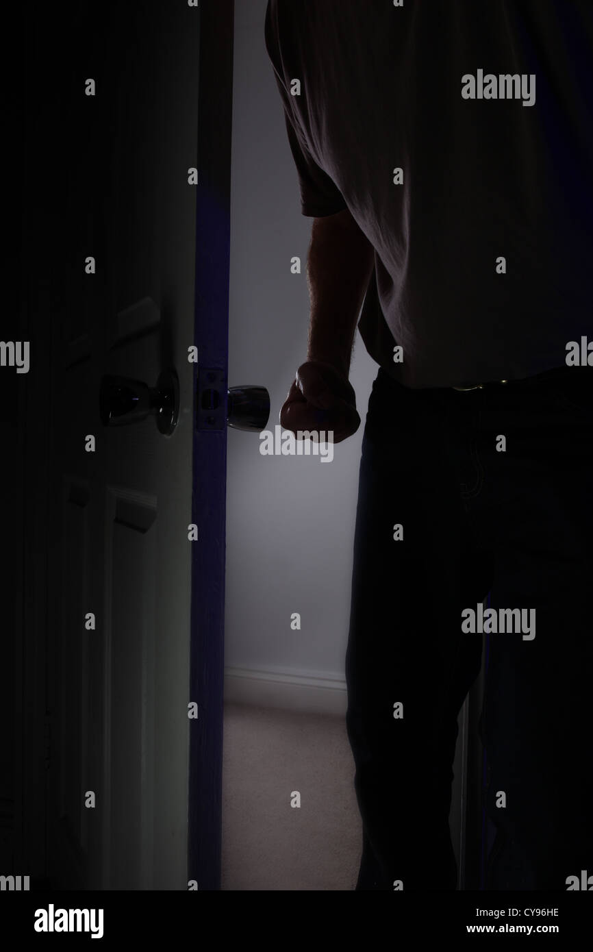 Male fist clenched entering a dark room. Model released - Stock Image