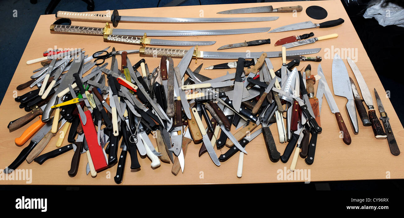 Table full of knives and swords collected by Sussex police after a knives amnesty Stock Photo