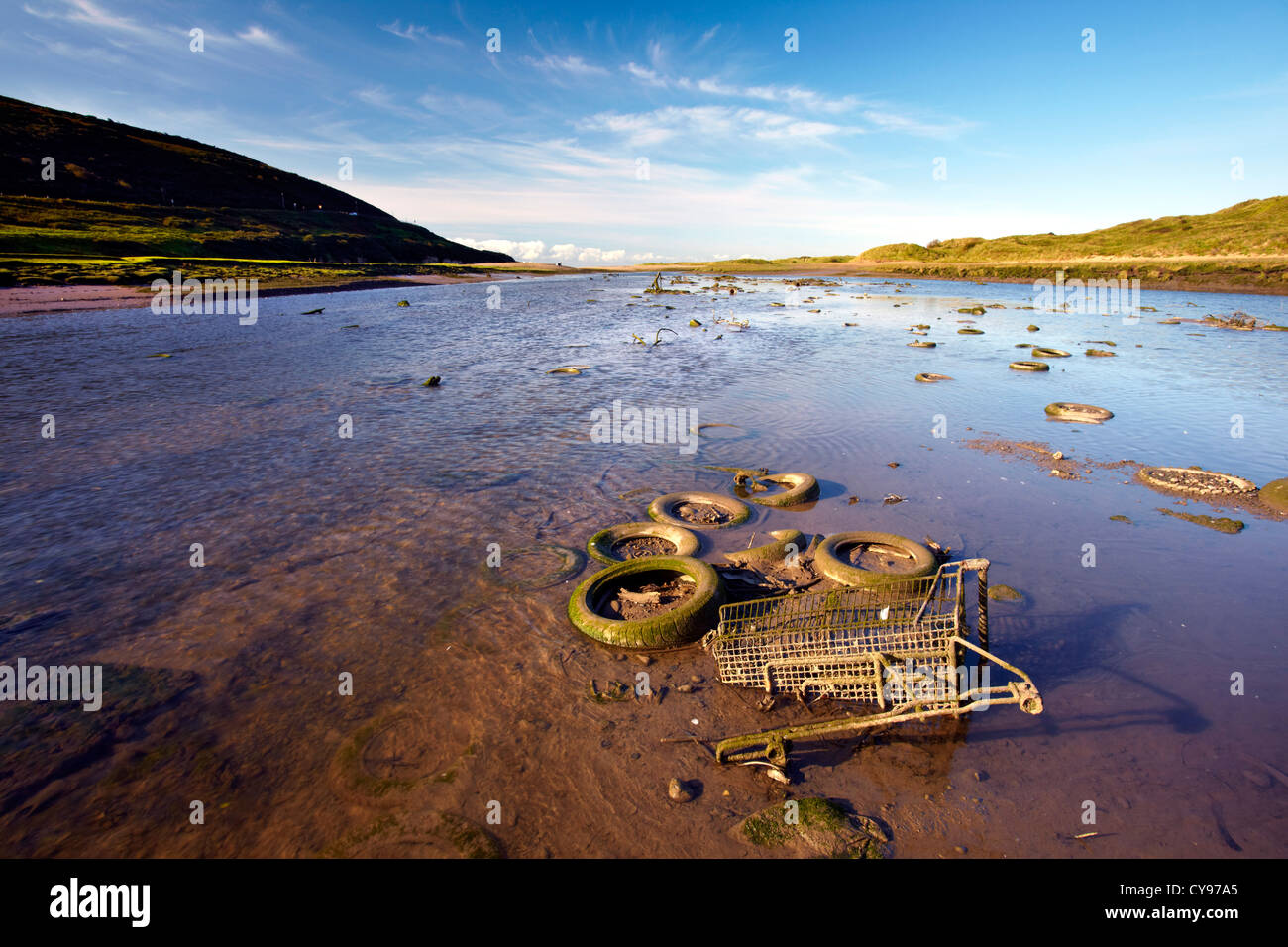Old shopping trolley and tyres in the estuary of the River Ogmore, Bridgend, South Wales - Stock Image