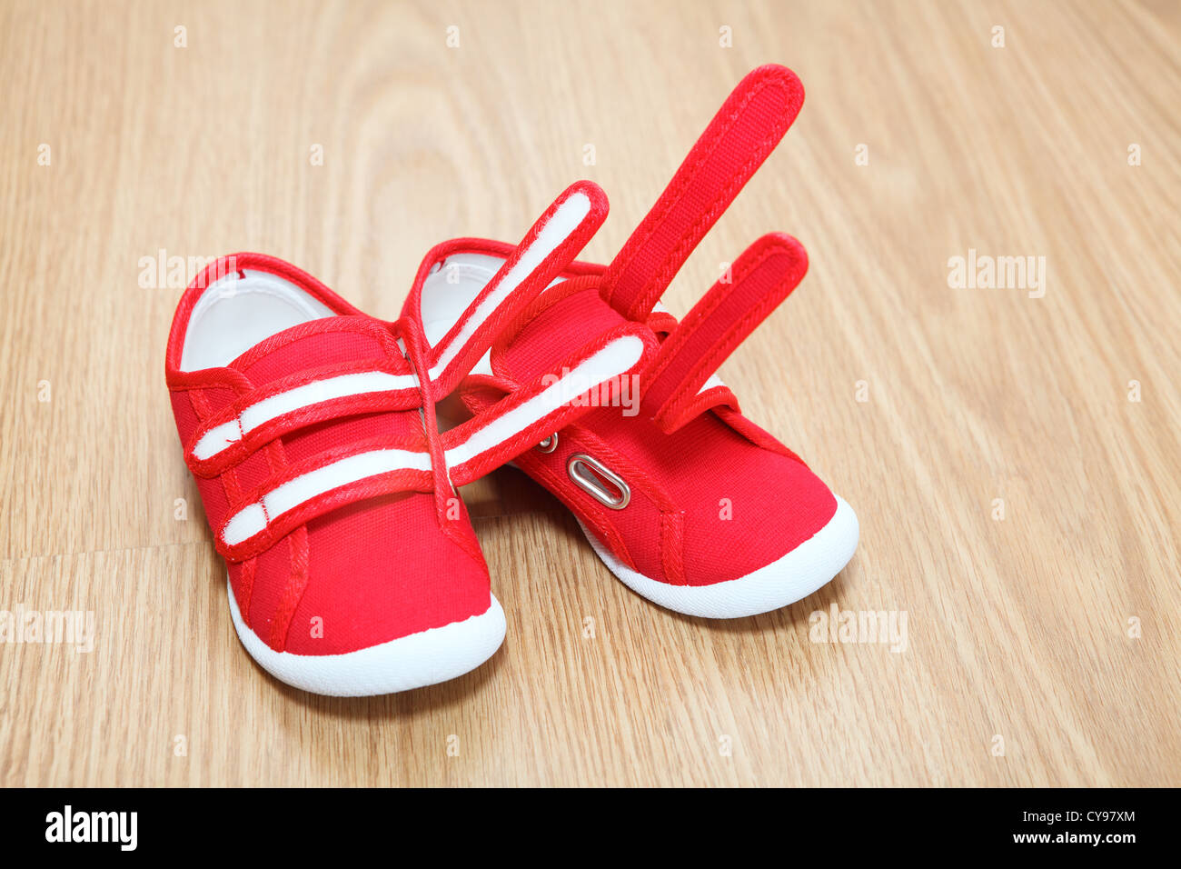 Red children shoes standing on the floor - Stock Image