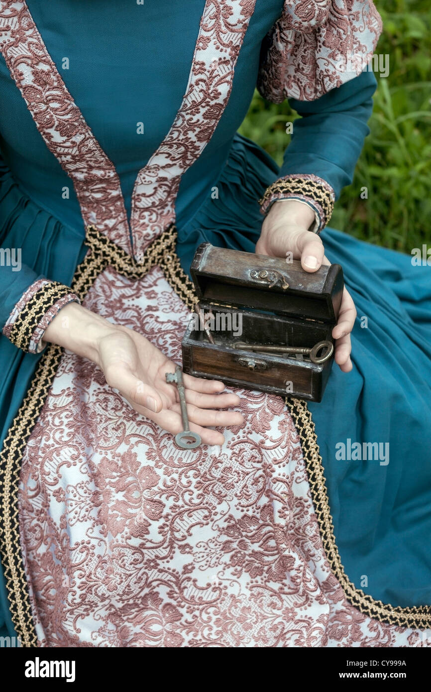 a lady in a renaissance dress holding a chest with old keys - Stock Image