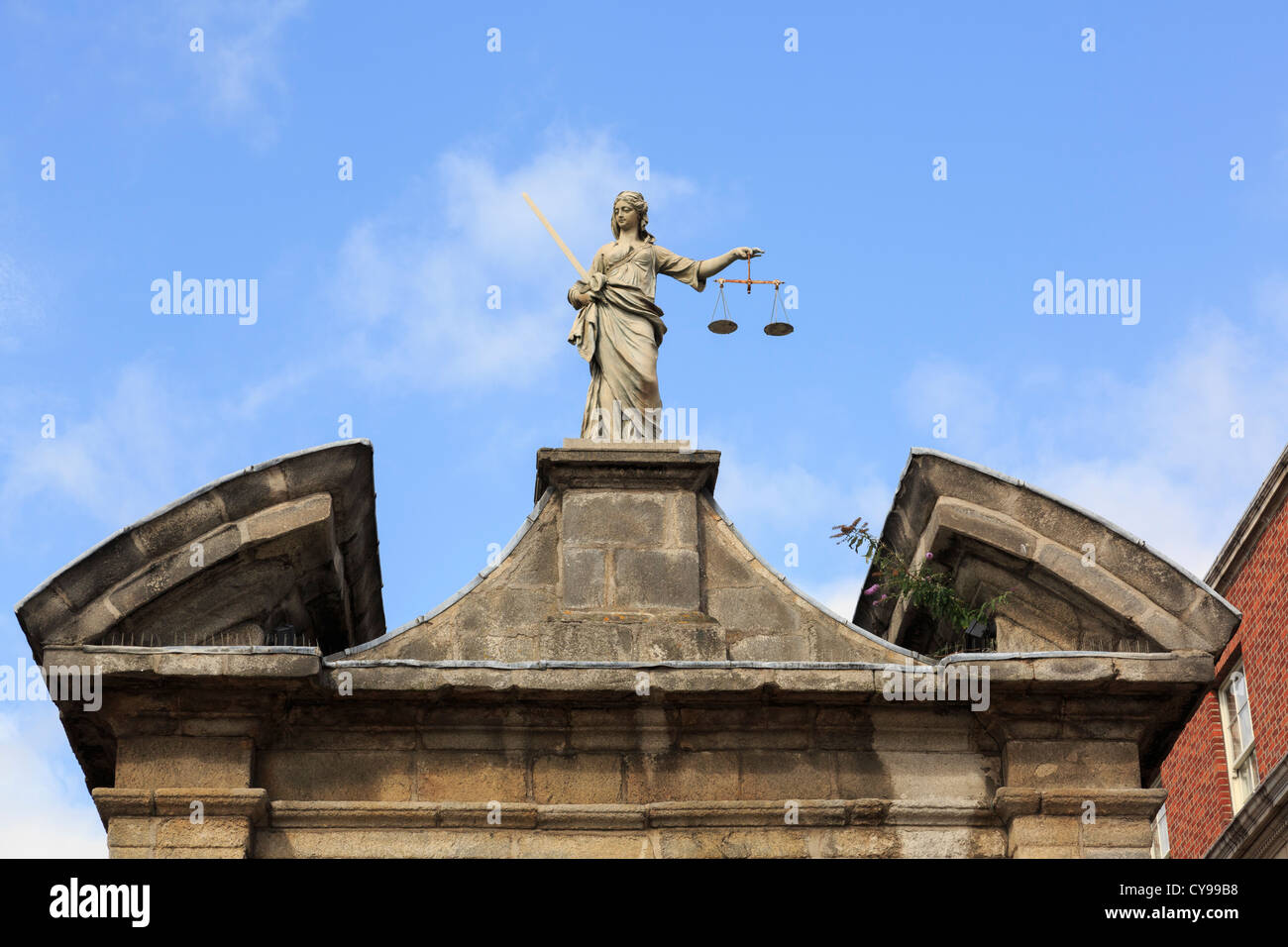 Statue of Lady Justice holding scales above an entrance gate in Dublin castle. Dublin, Republic of Ireland, Eire. - Stock Image