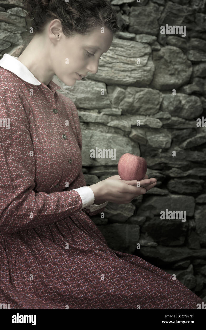 a woman with an apple - Stock Image