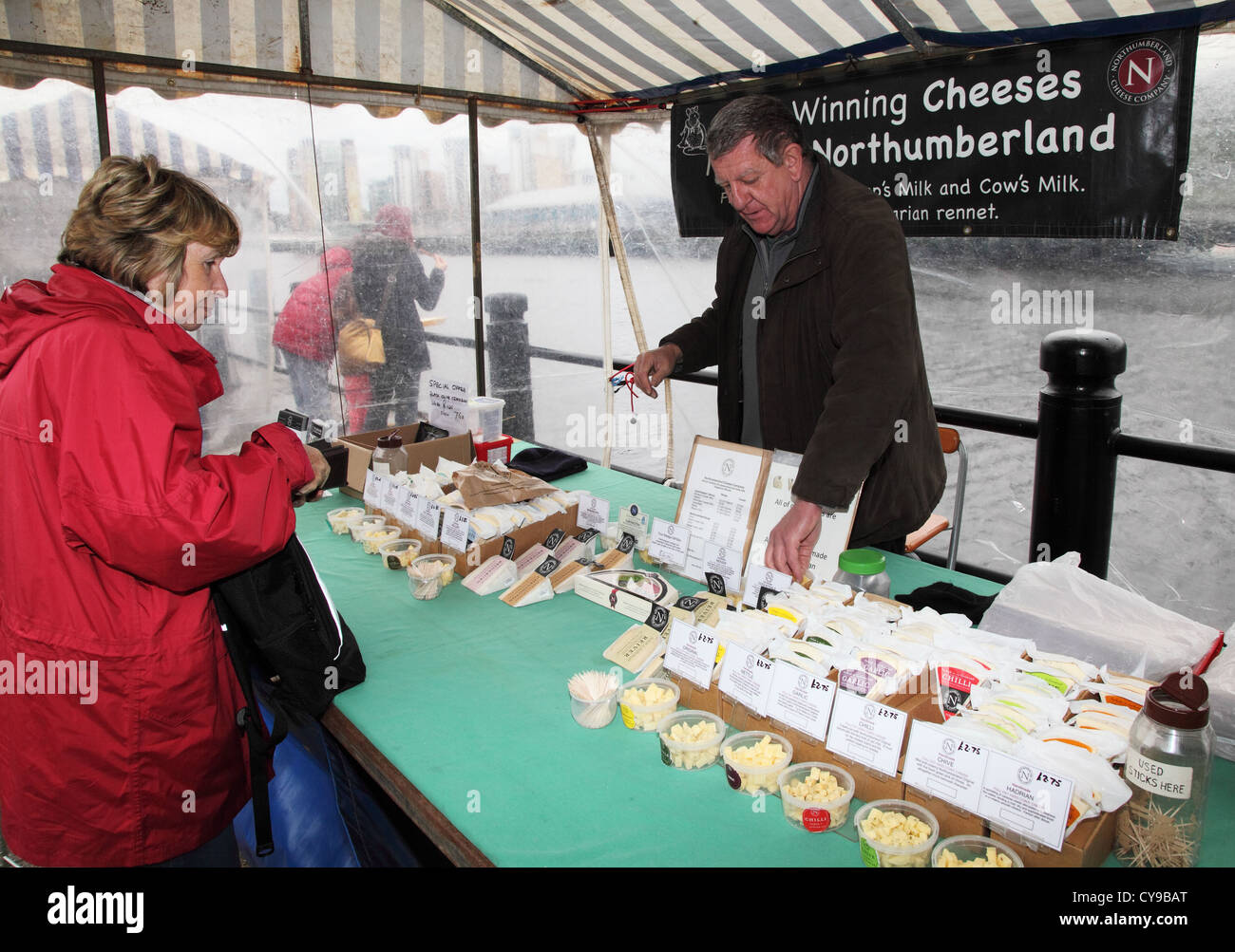 Man selling Northumbrian cheeses at a stall on Newcastle quayside market north east England UK Stock Photo
