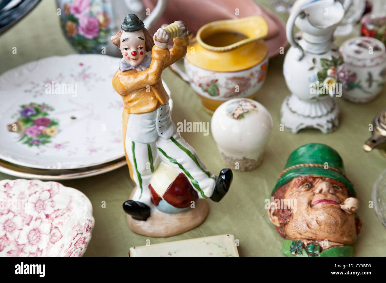 charming Victorian porcelain clown figurine with tiny bowler hat & squeeze box displayed with other china at - Stock Image