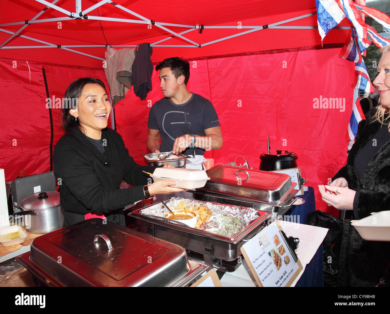 Smiling Asian woman serves Thai food to a customer at Durham City food festival, north east England, UKfoo - Stock Image