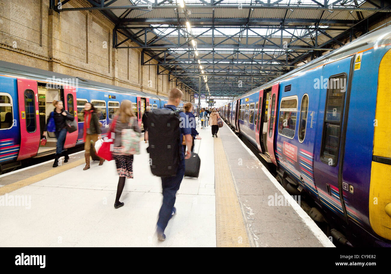 People rushing to catch a train,on the platform, Kings Cross station, London UK - Stock Image