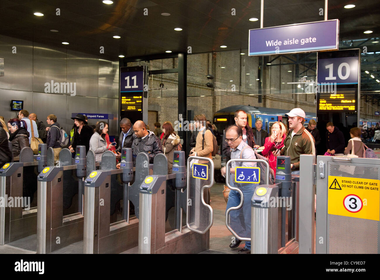 Rail passengers arriving by train and leaving the platform at Kings Cross station London, UK - Stock Image