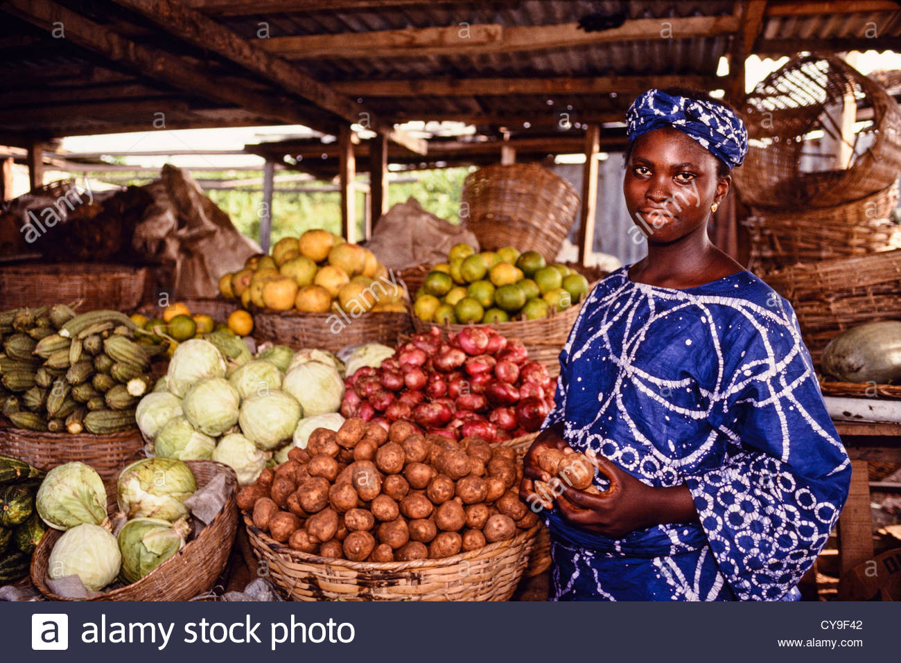 A Nigerian woman sells vegetables at an open air market near Lagos, Nigeria. - Stock Image