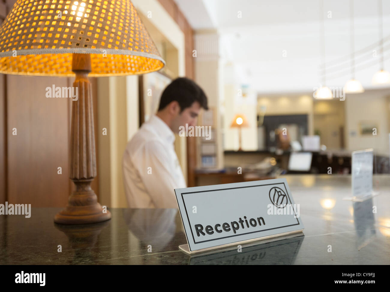 Hotel reception desk with a table and receptionists on a background - Stock Image