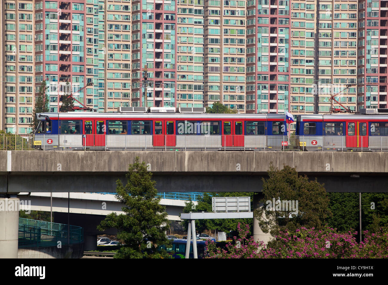 Light rail train passes residential blocks of flats between