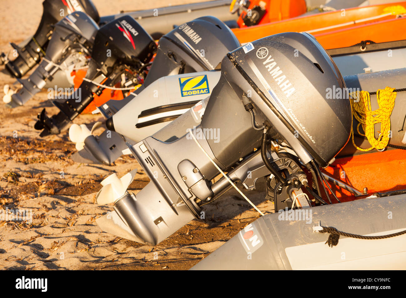 Outboard motors on safety boats on a beach on Lemnos, Greece. - Stock Image