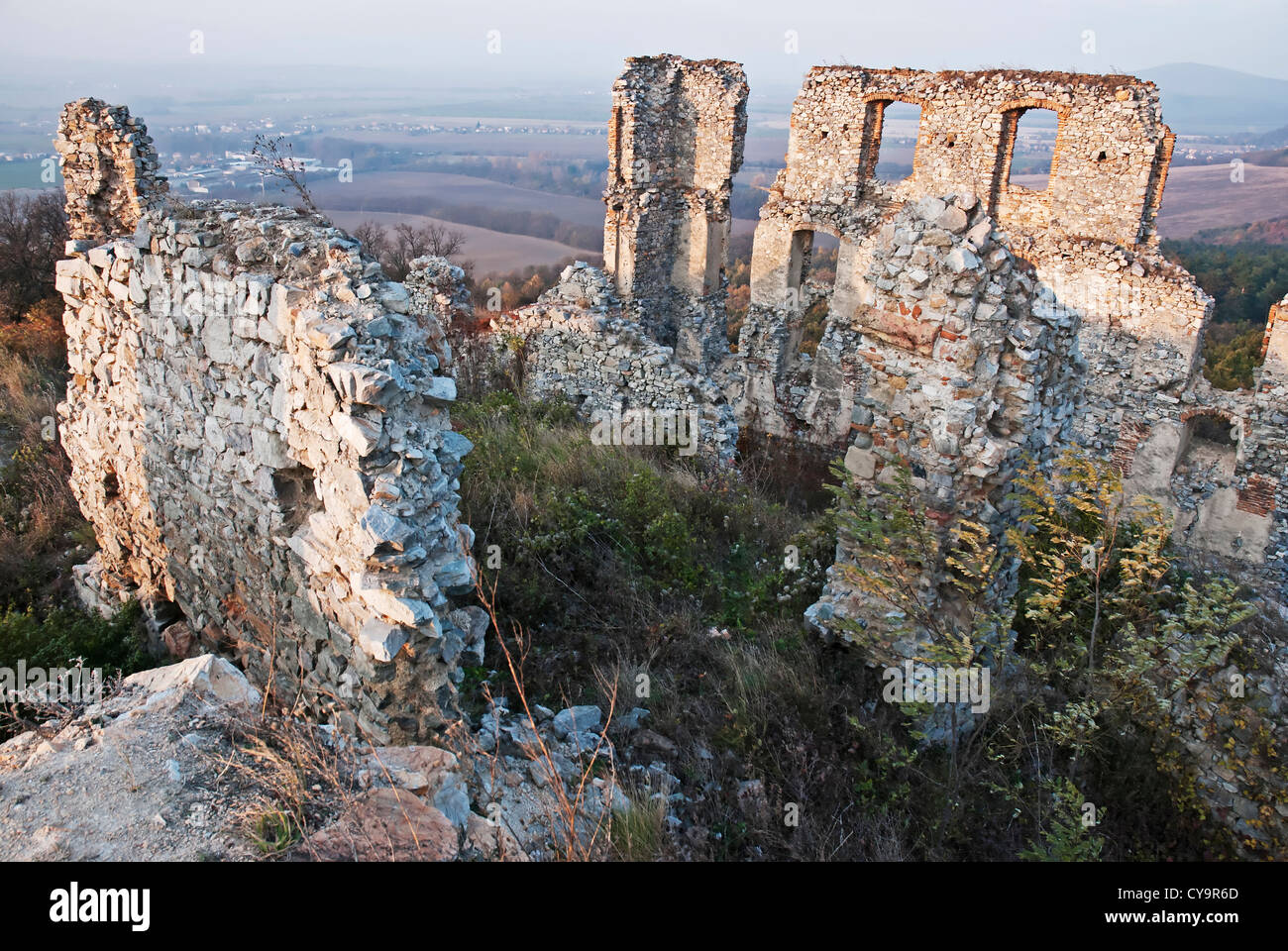 An old wall of ruined castle with a windows, sunset - Stock Image