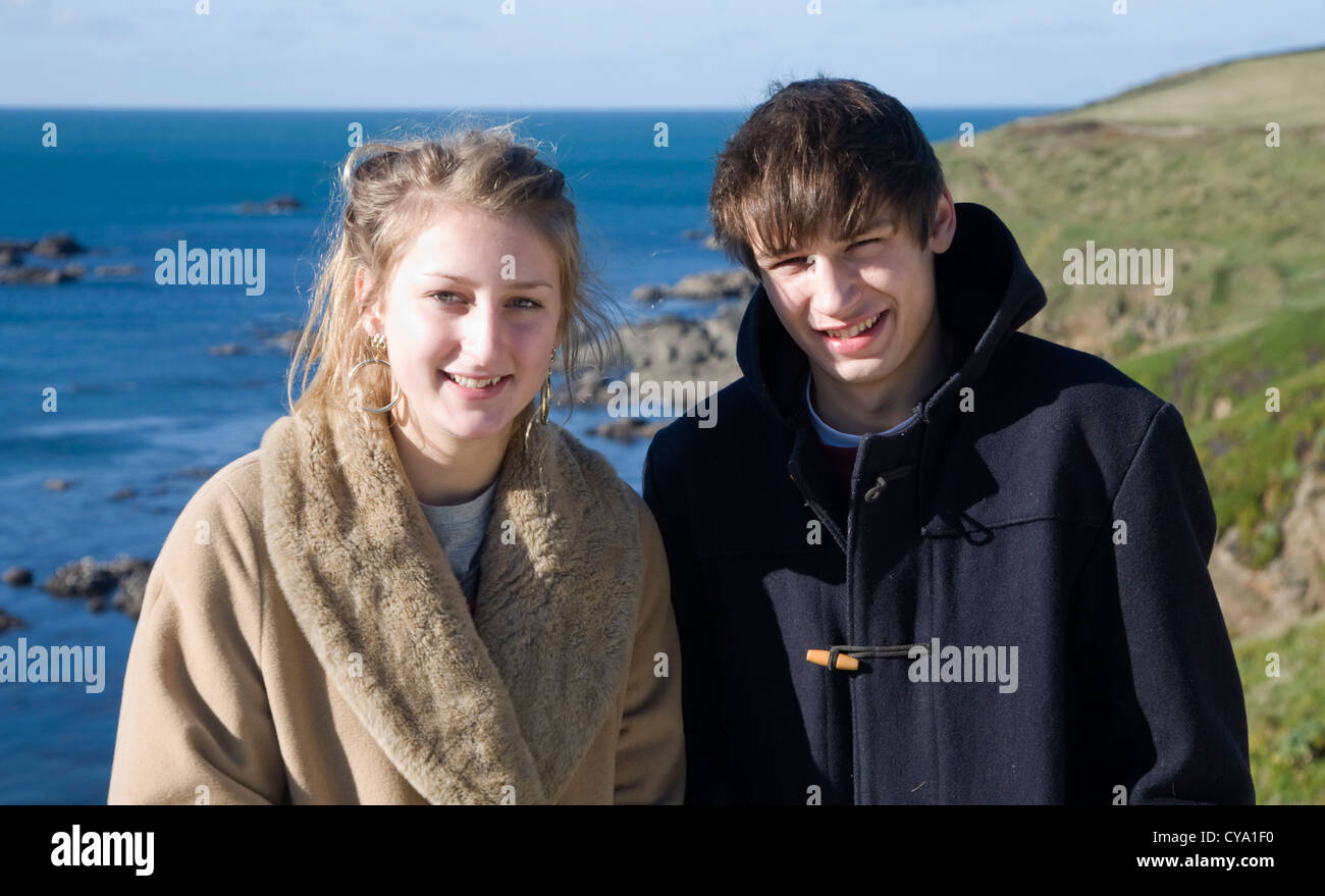Nineteen year old boy girl twins portrait outdoors by the sea in winter coats - Stock Image