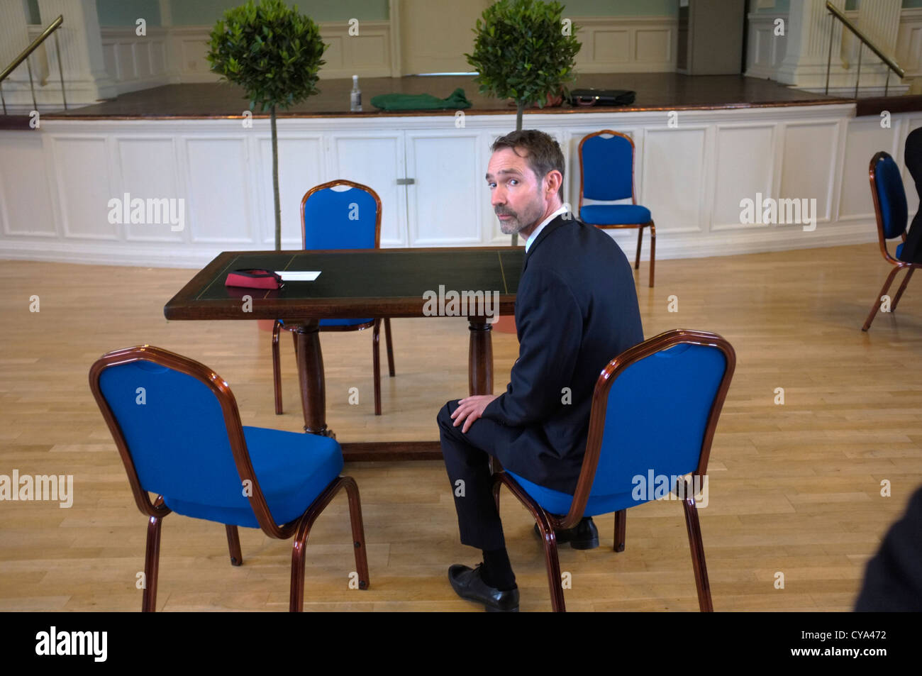 A nervous groom waits for his wedding ceremony to start in an English town hall - Stock Image