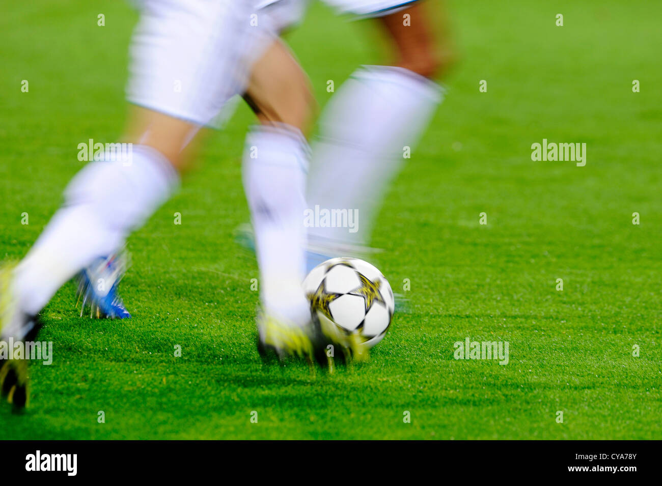 football players run by UEFA Champions League Balls Adidas Finale 12 OMB on football pitch - Stock Image