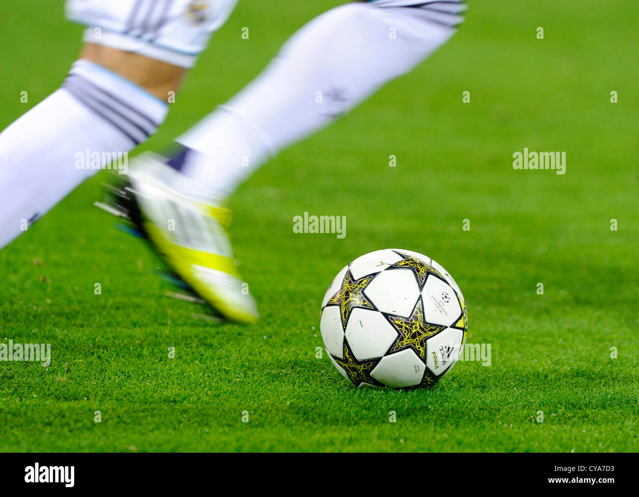 Legs of a Real Madrid Football player plays with UEFA Champions League Ball Adidas Finale 12 OMB on pitch - Stock Image