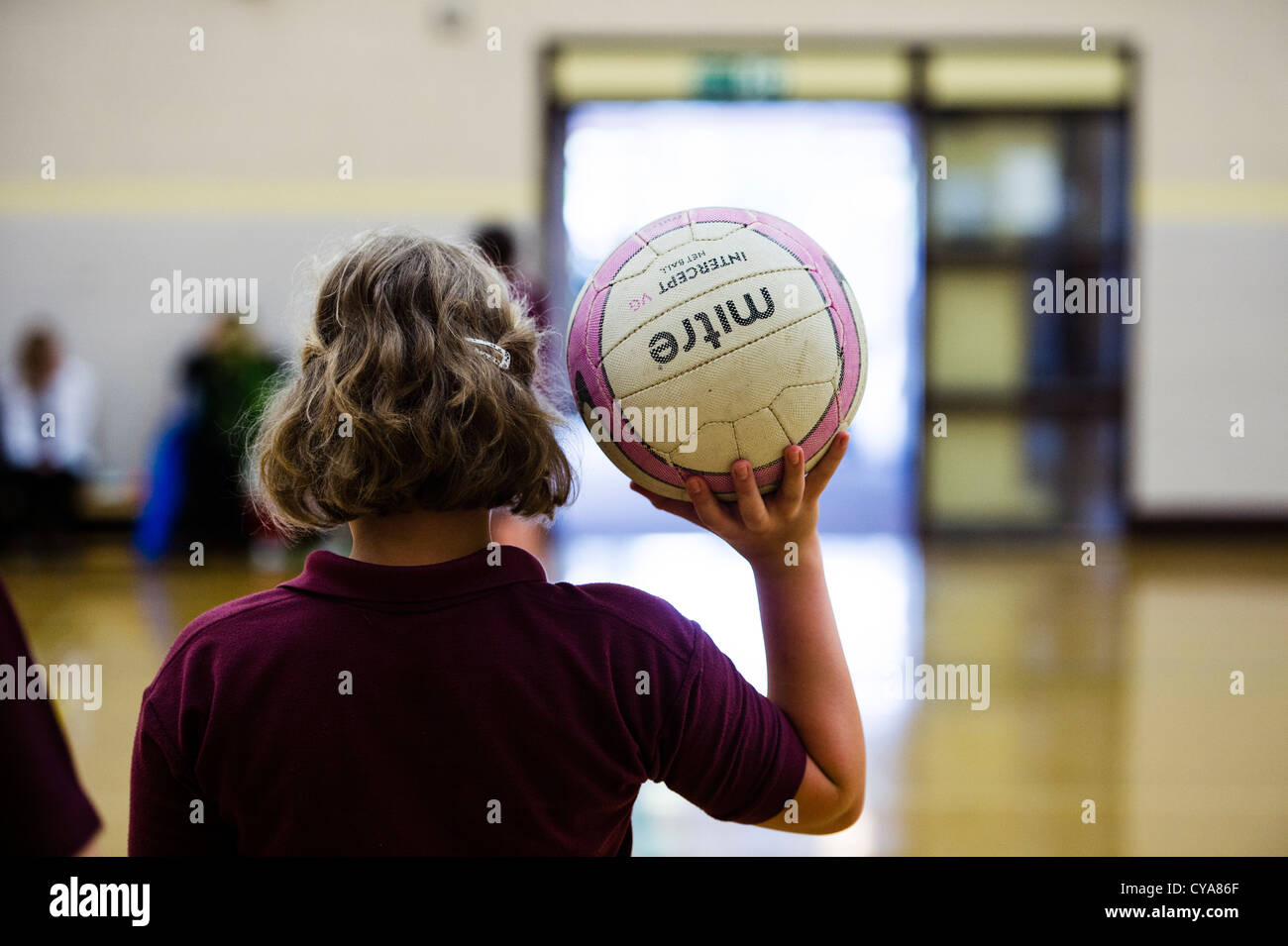 Rear view of a girl holding a netball in physical education lesson in a secondary comprehensive school UK - Stock Image