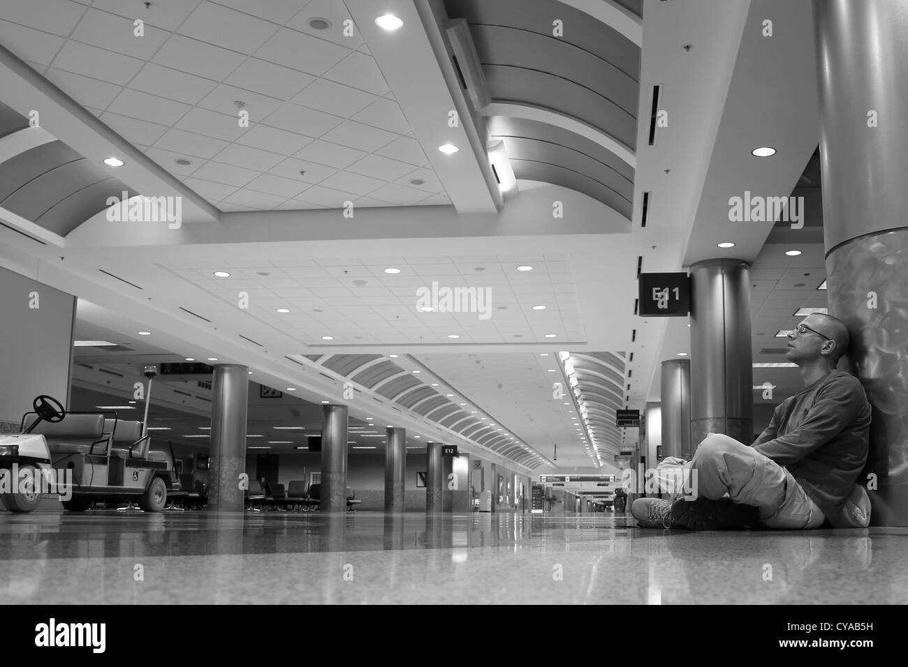 A man sitting alone in an empty airport terminal at Hartsfield-Jackson Airport, Atlanta, the busiest airport in - Stock Image
