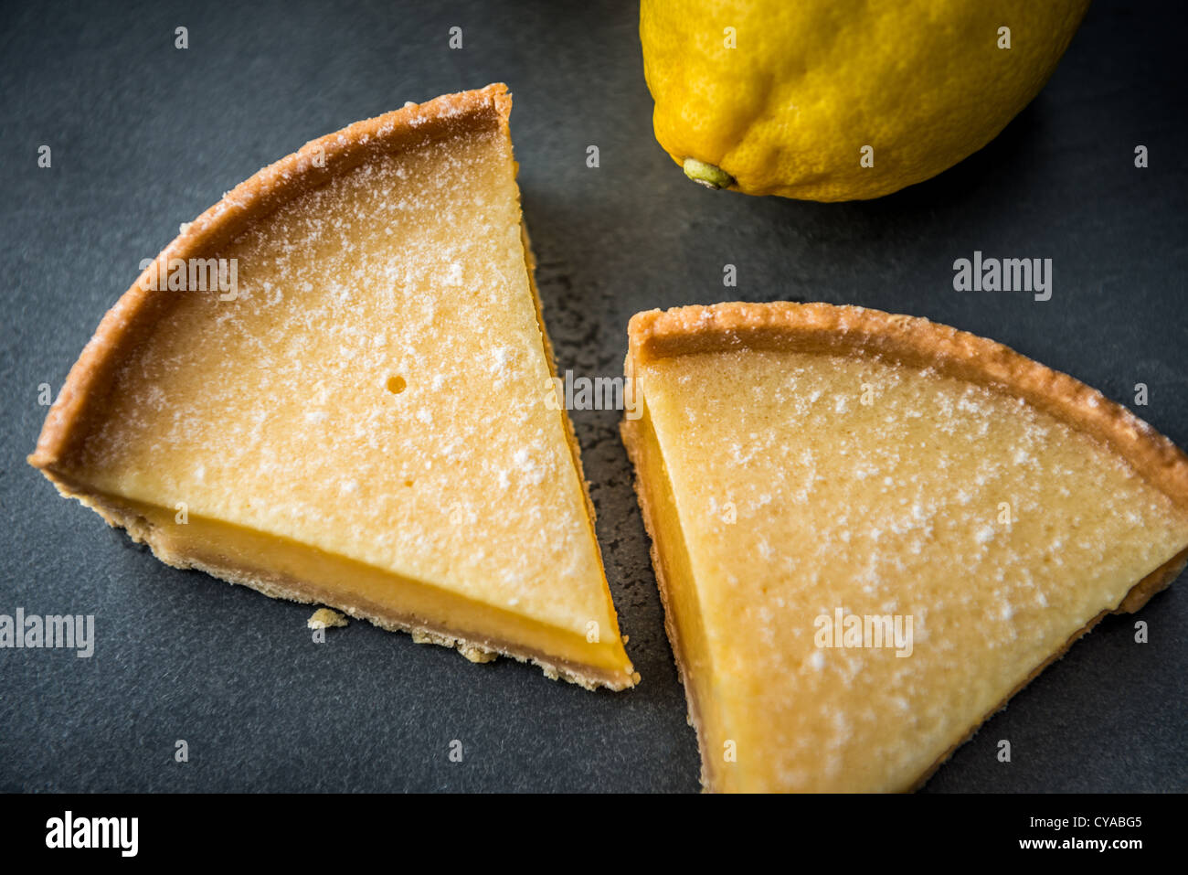 Lemon tart dessert with biscuit base on slate surface with lemons in background shot from above - Stock Image