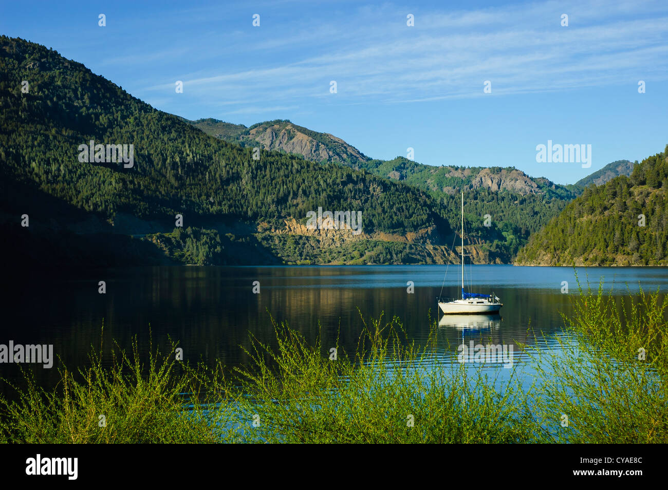 single small white sail boat on the Lácar Lake in the morning light near San Martin de los Andes in Argentina - Stock Image
