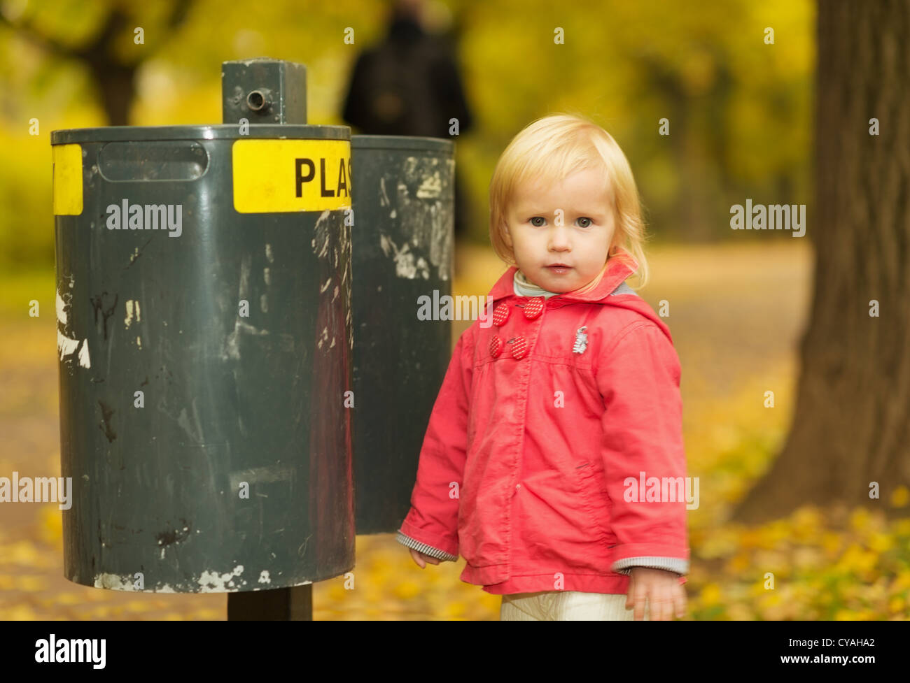 Portrait of baby near trash can - Stock Image