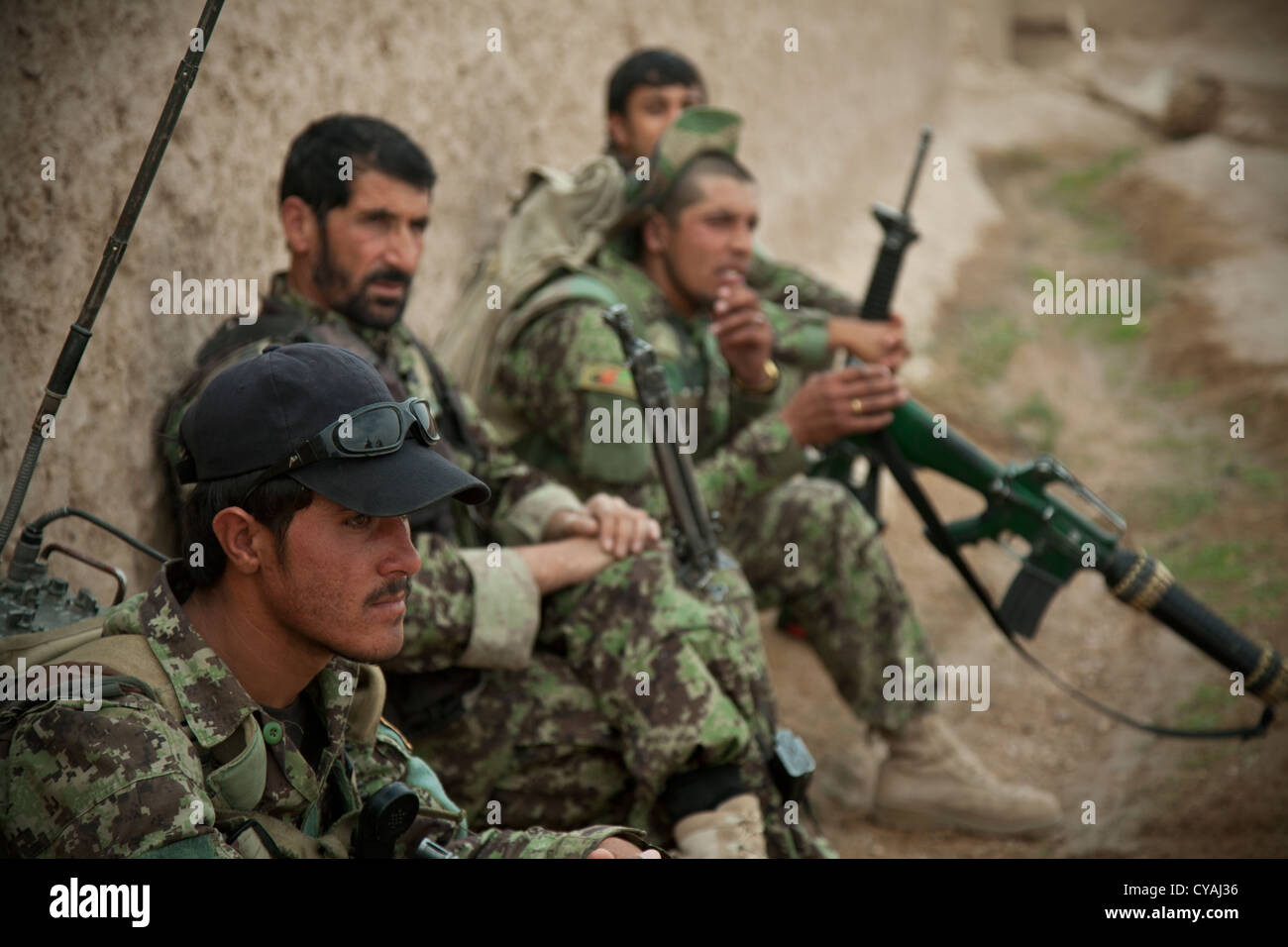 Afghan National Security Forces rest during a joint security patrol with coalition force members in order to deny - Stock Image