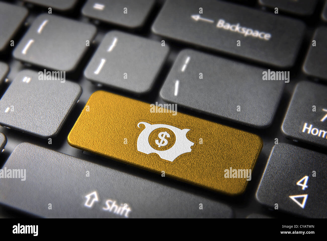 Make money with internet: golden key with piggy bank icon on laptop keyboard. Included clipping path, so you can Stock Photo
