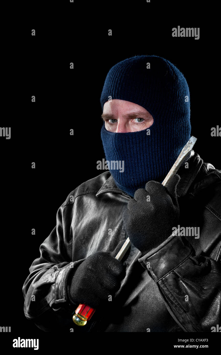 A criminal thief in a ski mask to hide his identity holds a large screwdriver as he prepared to commit a crime. - Stock Image