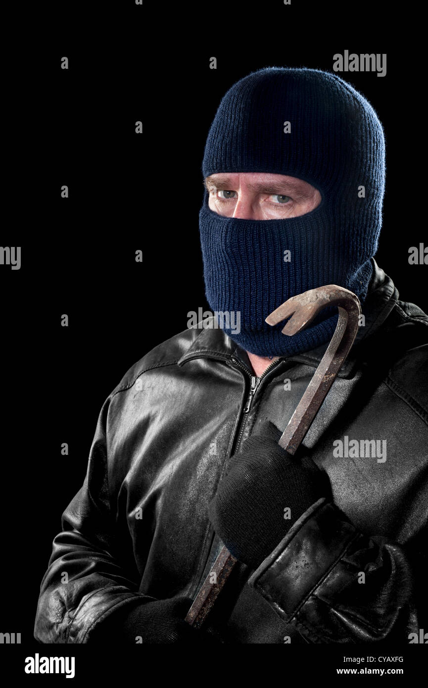 A thief wearing a ski mask to hide his identity holds a crowbar and prepares to commit a crime. - Stock Image