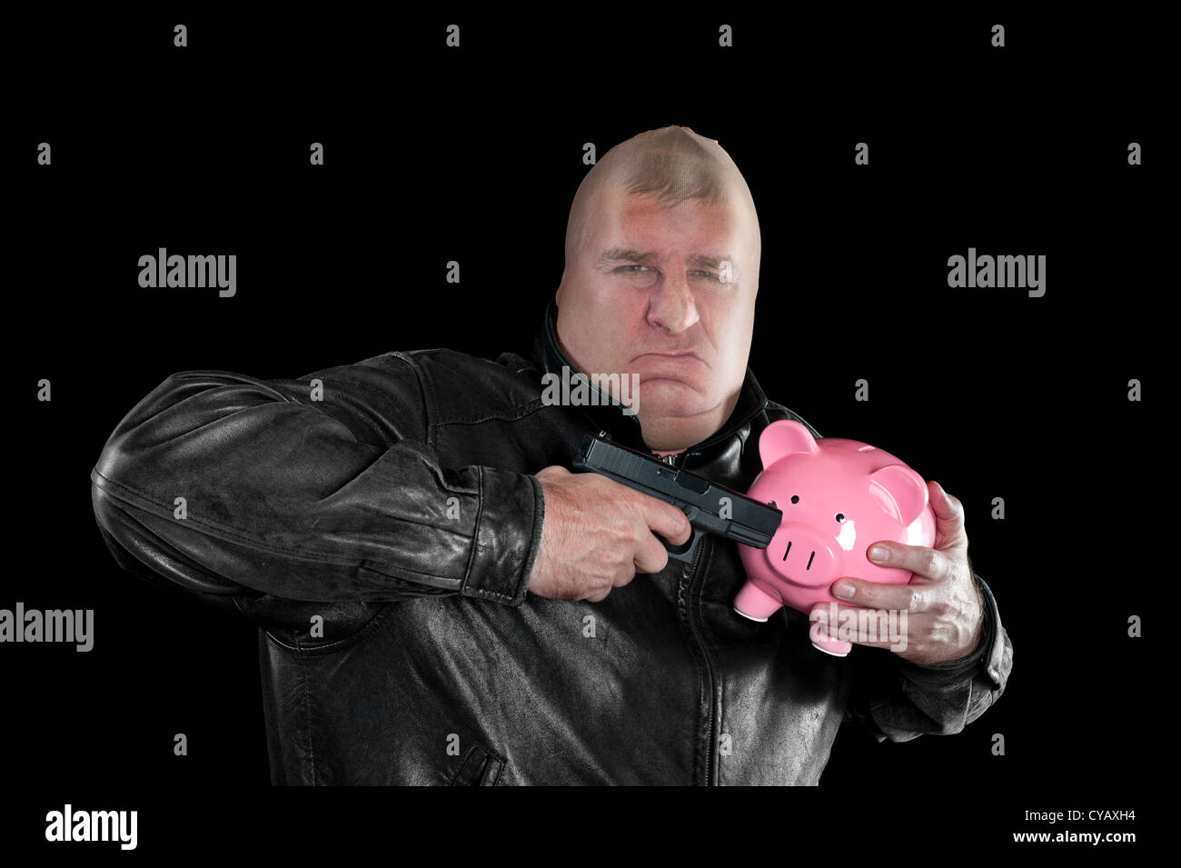 A masked thief threatening to shoot a piggy bank as he steals it during a bad economy. - Stock Image