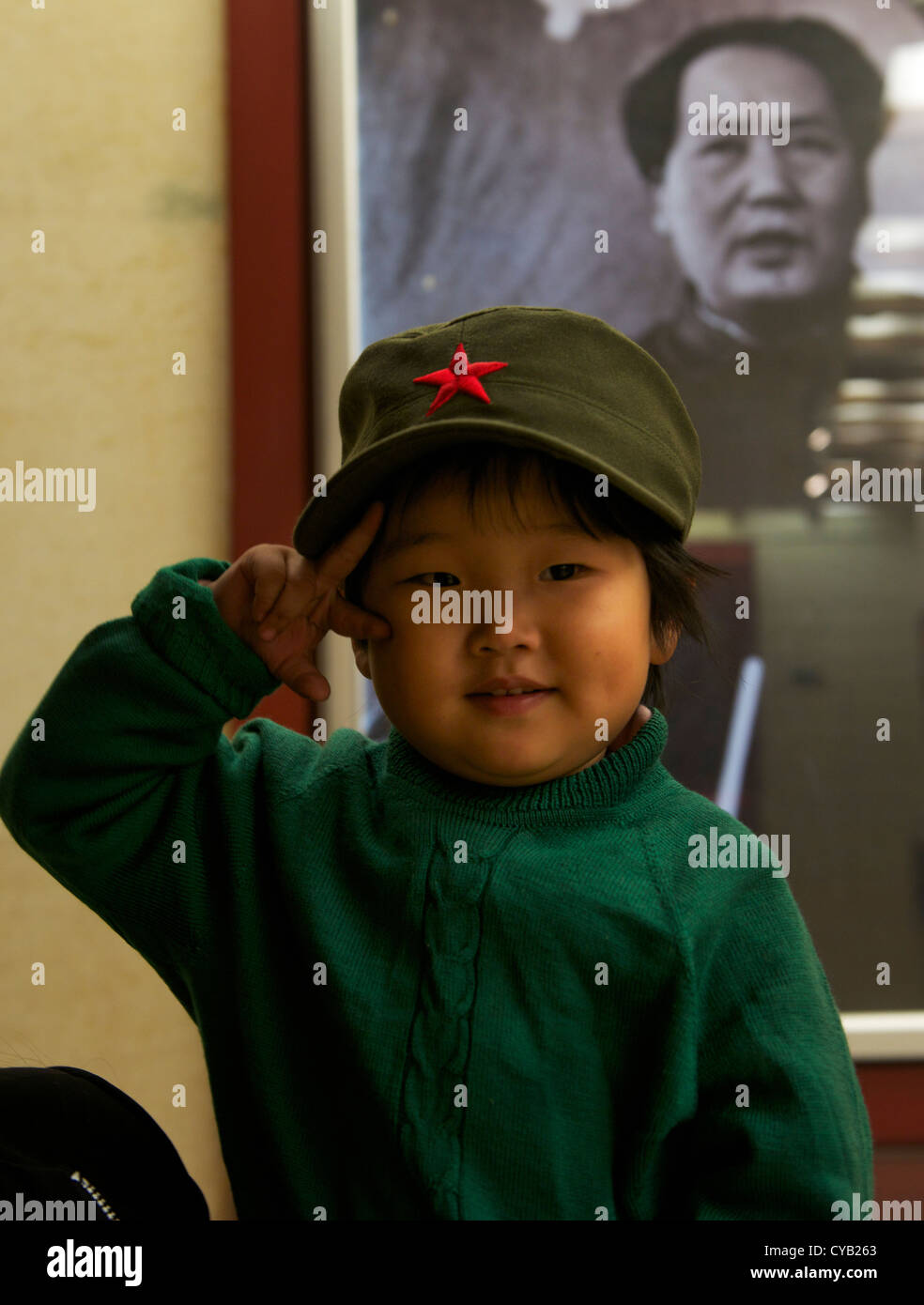 Chinese little girl poses in front of picture of Mao Zedong while visiting Xibaipo, one of Red Tourism spots in - Stock Image