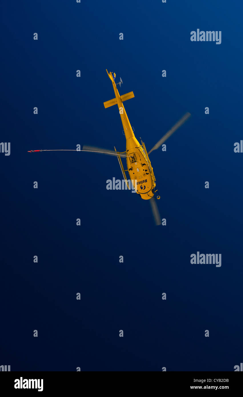 A bright yellow helicopter flies in ready to pick up it's precious cargo high up in the mountains. - Stock Image