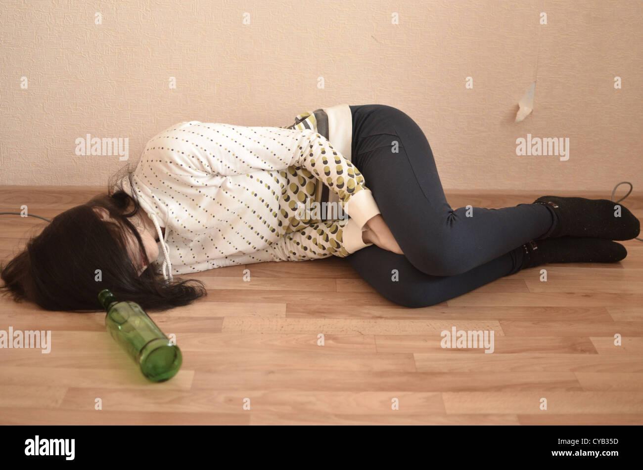 drunk woman lying on the floor - Stock Image