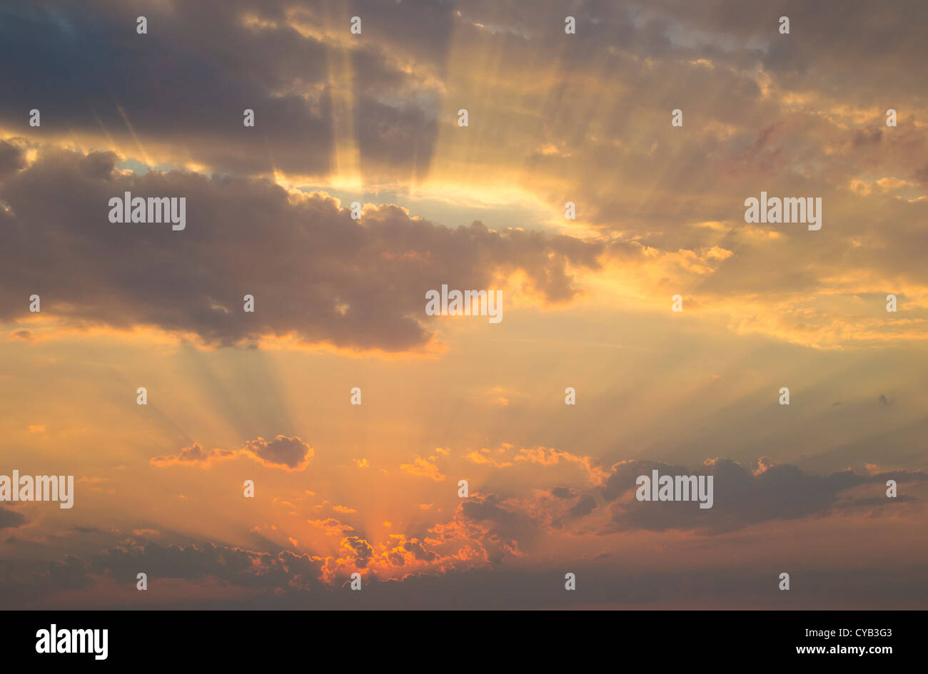 Heavenly rays of sunlight through a cloudscape above horizon of the calm sea Stock Photo