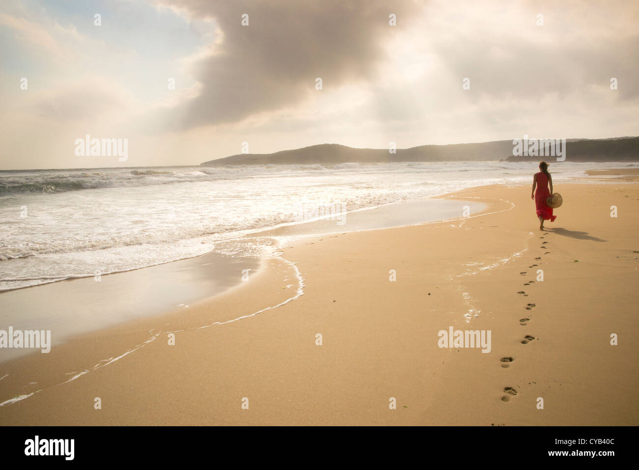 Young woman walk on an empty wild beach towards celestial beams of light falling from the sky - Stock Image