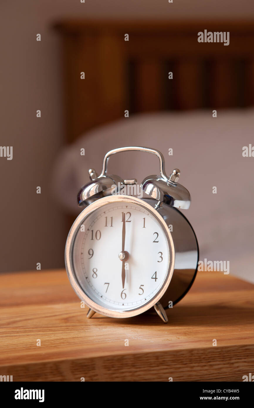 Alarm clock by bedside set at 6 AM Stock Photo