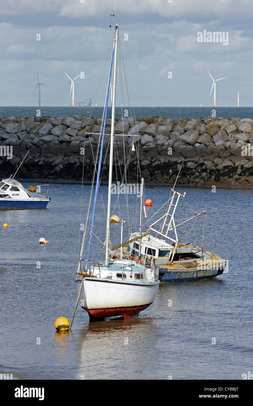 Boats moored behind the brake-water in Rhos on Sea, North Wales, with marine Wind Turbines on the horizon. - Stock Image