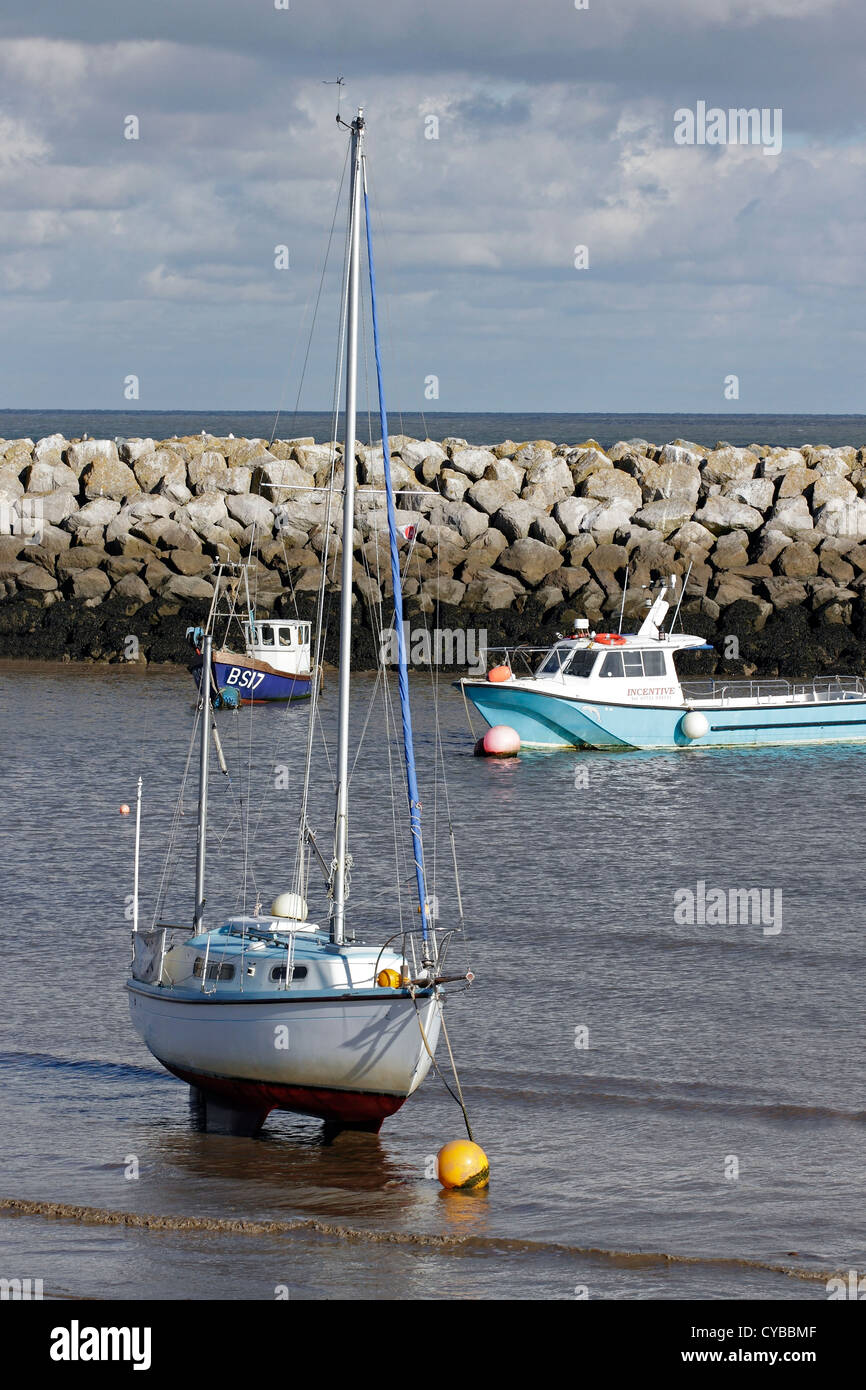 Boats moored behind the brake-water in Rhos on Sea, North Wales. - Stock Image