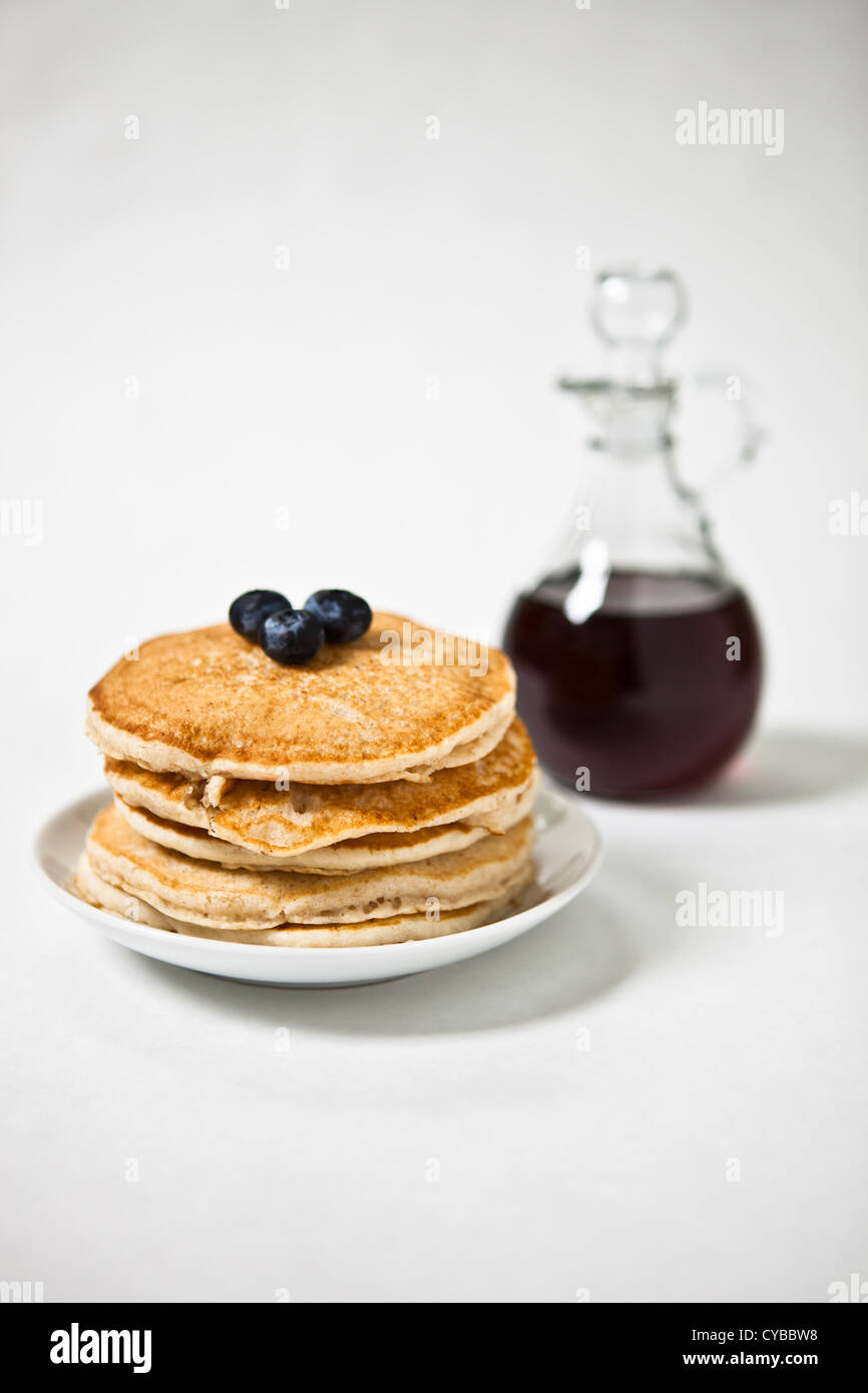 A stack of pancakes with blueberries on top - Stock Image