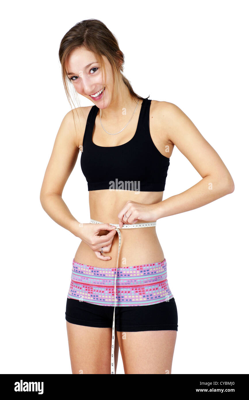 Pretty, sporty and fit young woman in work out clothes happy over waist measurements, perfect for health issues. - Stock Image