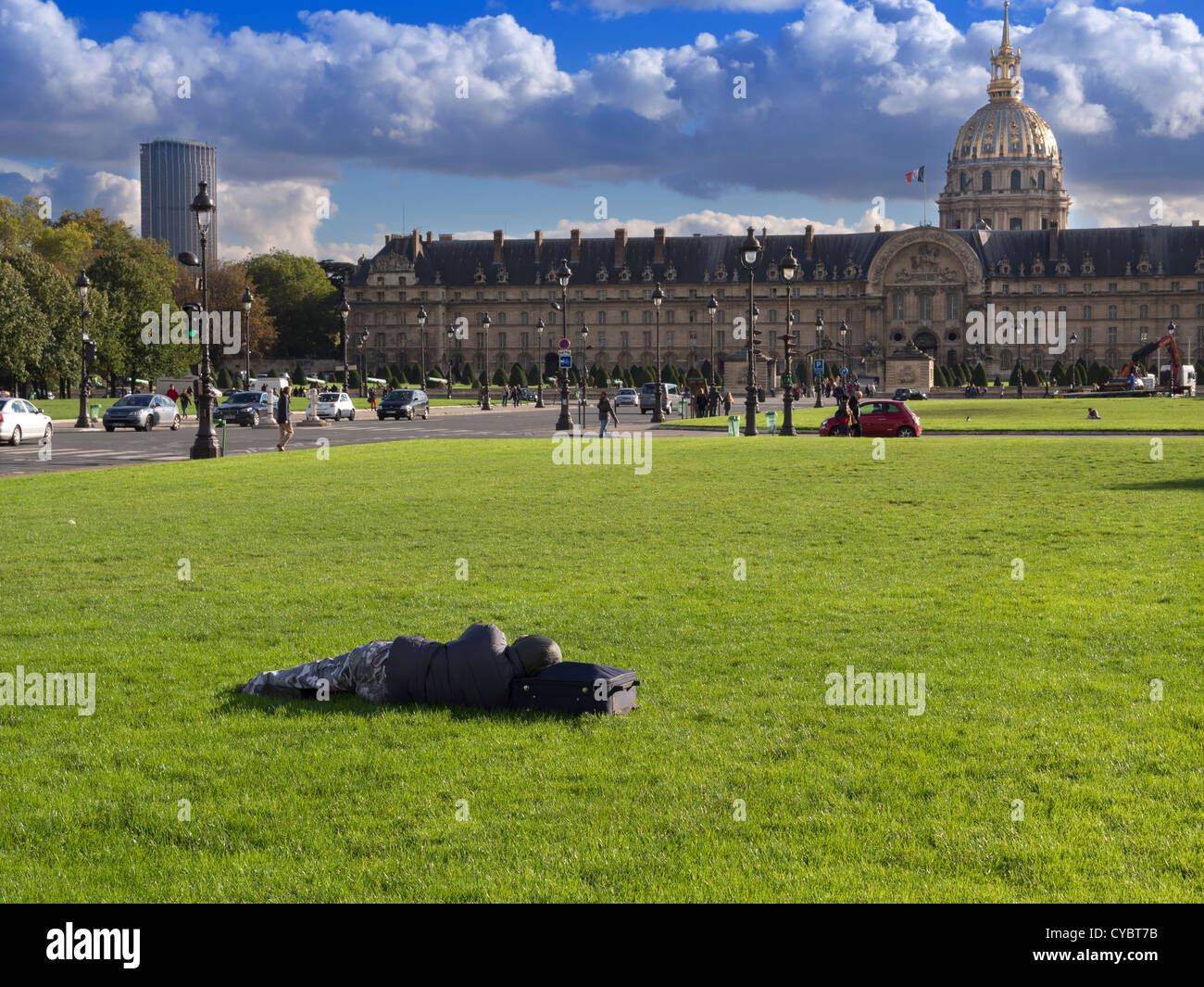 Homeless person sleeping on the grass in front of Les Invalides, Paris - Stock Image