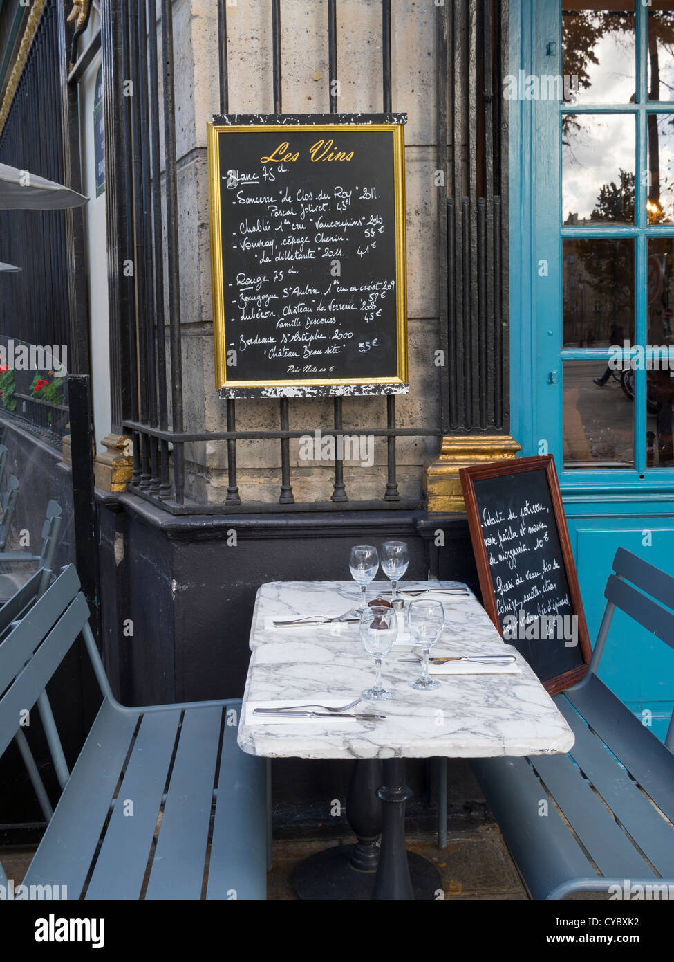 Chalkboard above tables and benches at an outdoor cafe in Paris Stock Photo