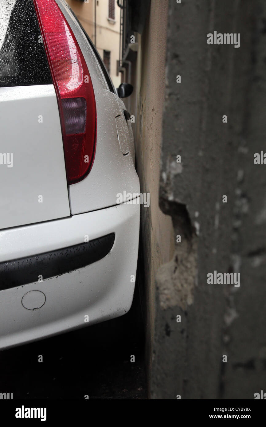 Сar is parked is very close to wall of the house. Florence (Firenze), Italy. Shallow DOF. - Stock Image