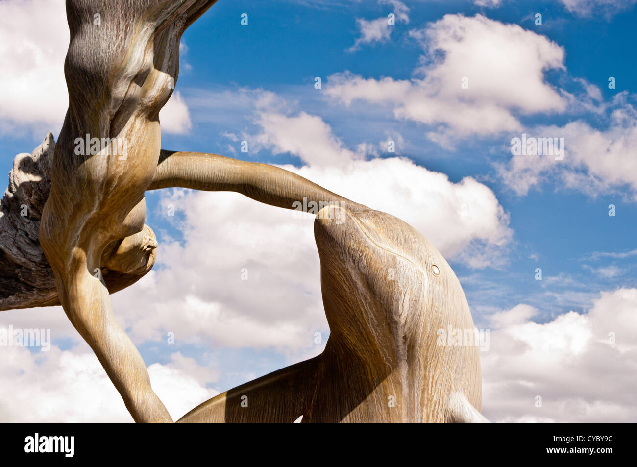 Dolphin Statue against the blue sky and white clouds - Stock Image
