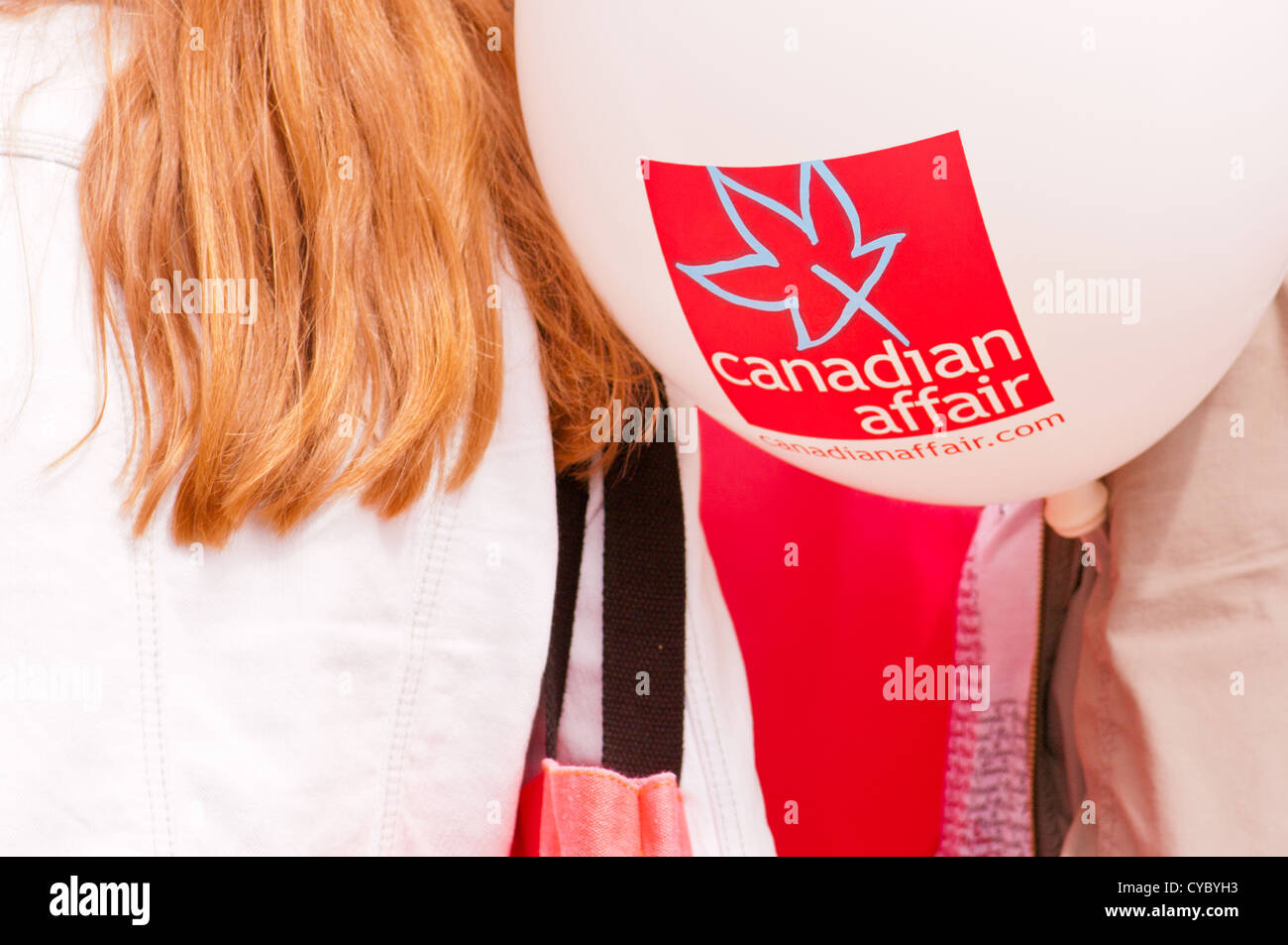 Back of girl with white balloon and canadian logo canidian affair - Stock Image