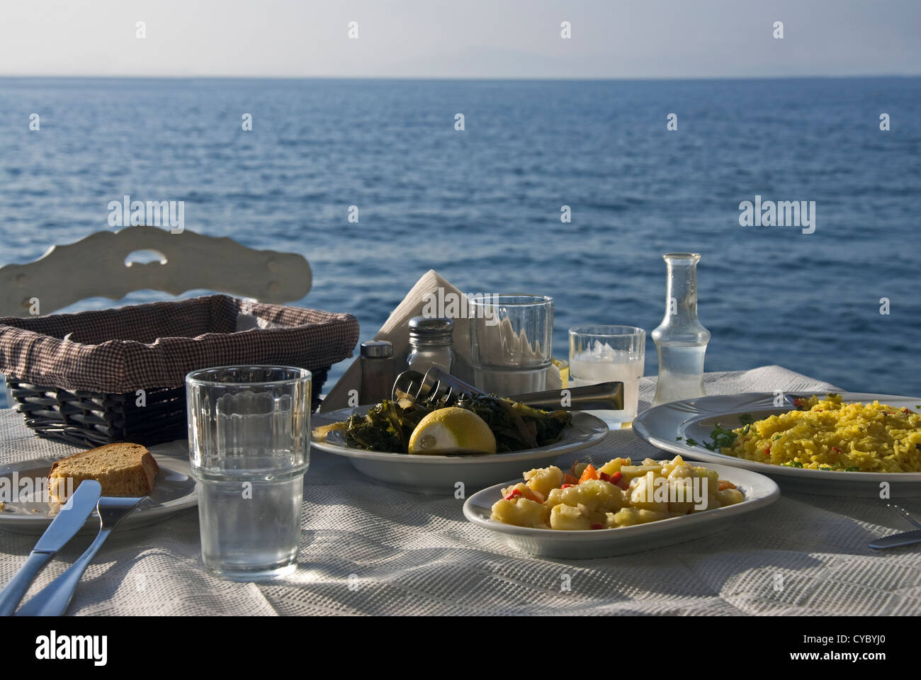 Laid table by the sea in Greek taverna (Greece) - Stock Image