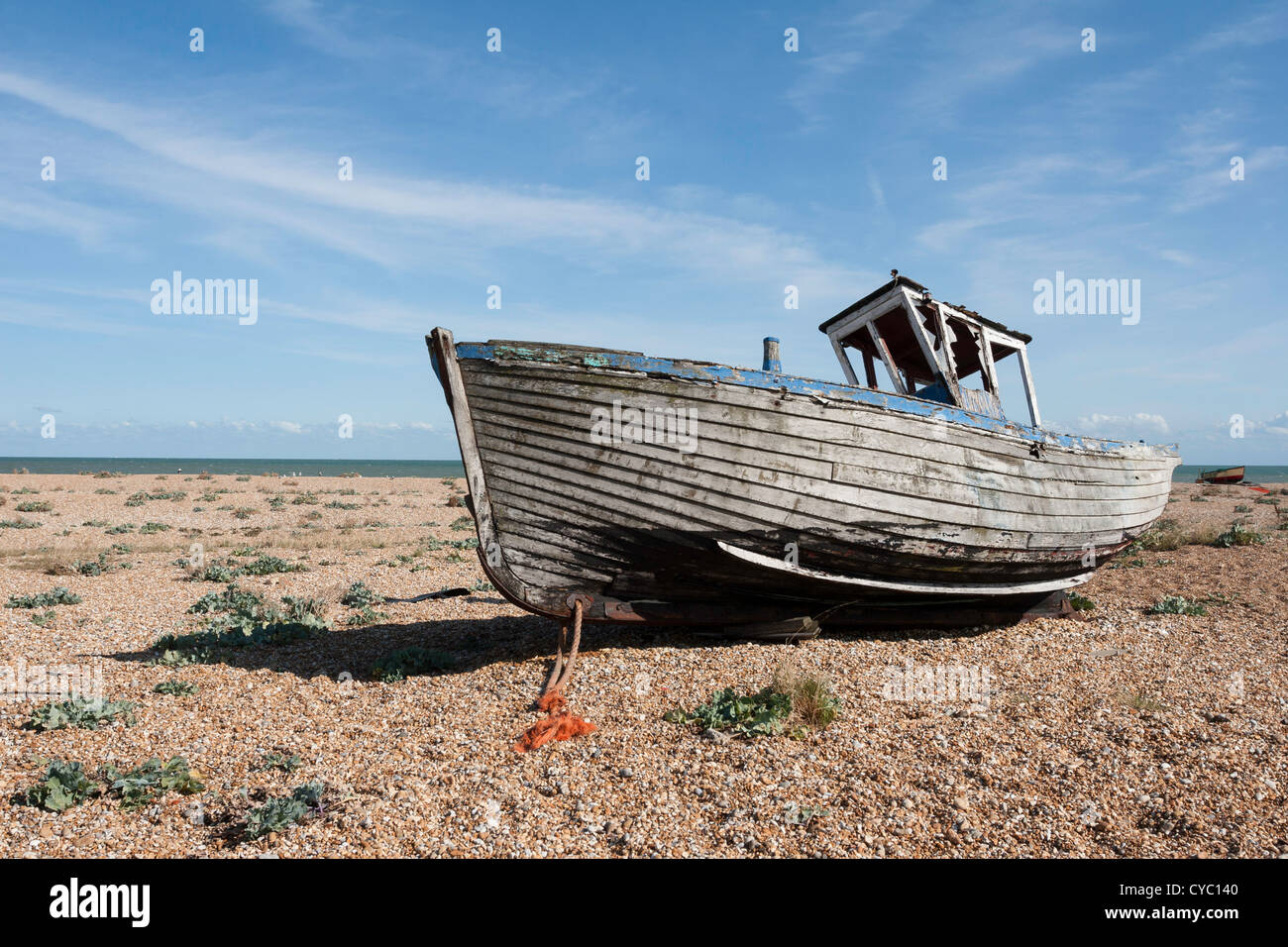Old fishing boat marooned on the shingle beach at Dungeness in Kent - Stock Image